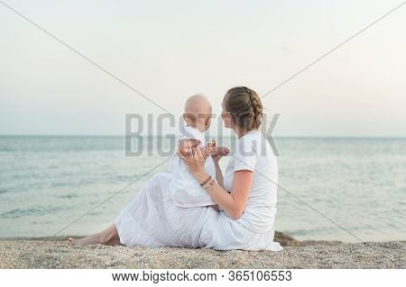 Young Mother And Toddler Sitting On The Sandy Shore Of Sea Background. Motherhood, Harmony And Love.