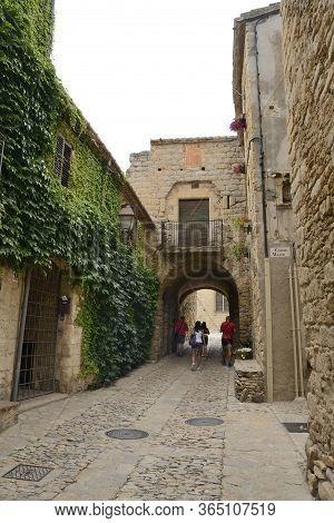 Peratallada, Spain - July 25, 2017: People Passing By Passageway At Cobbled Street Of The Medieval V