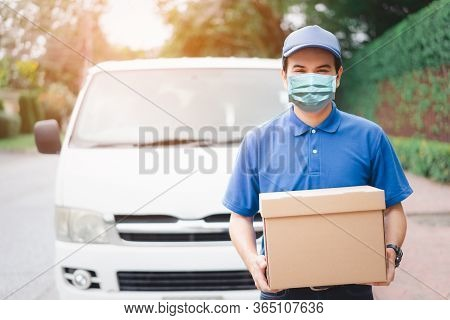 Postal Delivery Courier Man Wearing Protective Face Mask In Front Of Cargo Van Delivering Package Ho