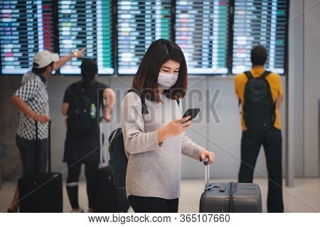 Young Asian Woman Traveler Using Smartphone And Holding Luggage While Waiting Check-in At Terminal I