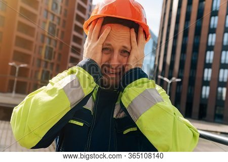 Spastel Young Man In A Helmet Close-up, Upset In Shock, Holding His Head. The Concept Of Saving Peop