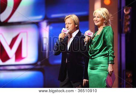 MOSCOW - DEC 17: Dmitry Haratian, Tatiana Vedeneeva tv presenters on scene concert of Legend RetroFM in Sports complex Olimpiyskiy, on Dec 17, 2011 in Moscow, Russia.