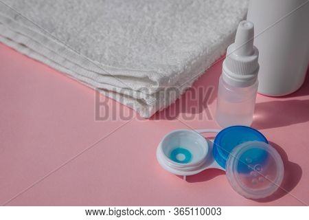 The Lens Container Is Open And Contains A Blue Contact Lens. The Lid Is Next To It. Next To It Is A