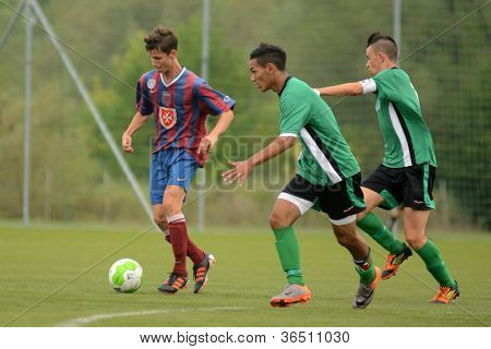 KAPOSVAR, HUNGARY - SEPTEMBER 1: Viktor Somogyi (C) in action at the Hungarian National Championship under 18 game between Kaposvar (green) and Videoton (blue) September 1, 2012 in Kaposvar, Hungary.