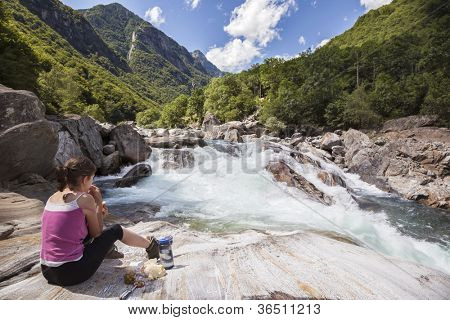 Woman having picnic on beautiful mountain riverside in Switzerland, Verzasca Valley.