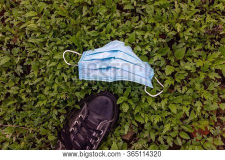 Used Surgical Mask Dumped On The Grass During The Covid-19 Pandemic. Discarded Face Mask Used To Pro