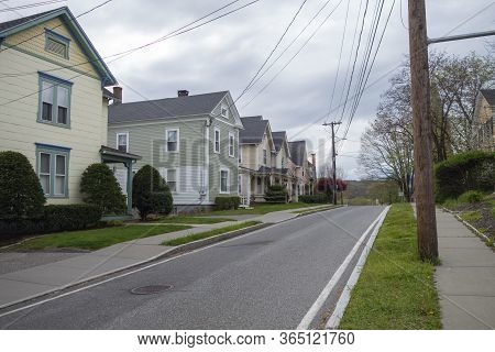Street Of Suburban Homes In A Row And Trees And Blacktop Road And Walkway