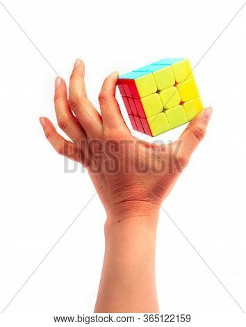 Italy, Milano - 10 April 2020: A Hand Holding Rubik's Cube Puzzle, Isolated On White Background.