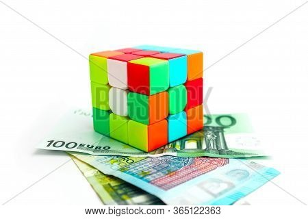 Italy, Milano - 10 April 2020: Rubik's Cube Puzzle, Isolated On White Background. Euro Paper Money A