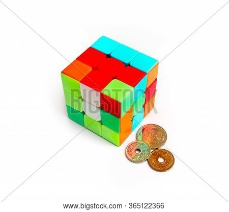 China, Wuhan - 1 May 2020: Rubik's Cube Puzzle And Asian Coins, Isolated On White Background. Chines