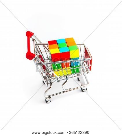 Italy, Milano - 10 April 2020: Shopping Cart With Colorful Puzzle Cube Isolated On White Background.