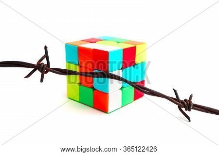 Italy, Milano - 1 May 2020: Rubik's Cube Puzzle And Barbed Wire, Isolated On White Background. Restr