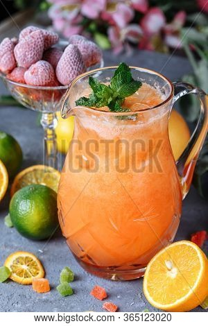 Summer Fresh Cold Drink Beverages. Ice Lemonade In The Jug And Lemons And Orange With Mint On The Ta