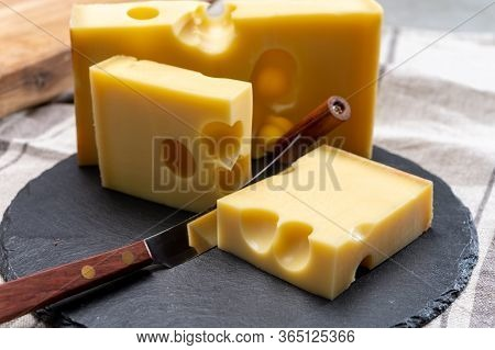 Block Of Swiss Medium-hard Yellow Cheese Emmental Or Emmentaler With Round Holes And Cheese Knife Cl