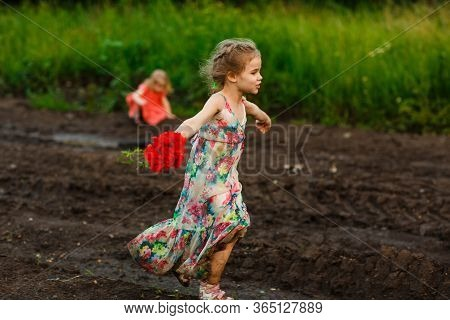 Little Girl In A Dress Goes In The Dirty Dirt Road. Earth After A Rain. Off-road. Near A Field With