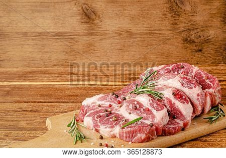 Sliced Pork Meat On Chopping Board With Pepper And Rosemary On Wooden Background. Copy Space