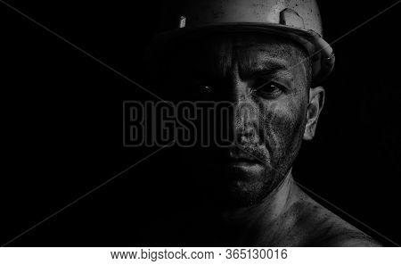 Dirty Coal Miner In A Yellow Hard Hat On A Dark Background In A Black And White Photo