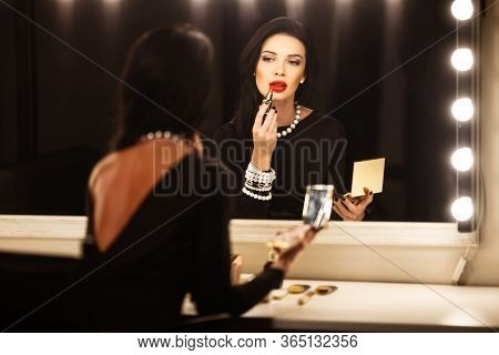 Jewelry and beauty concept - beautiful brunette lady portrait in modern gems and black dress in studio. Woman sits by the makeup mirror and puts on red lipstick