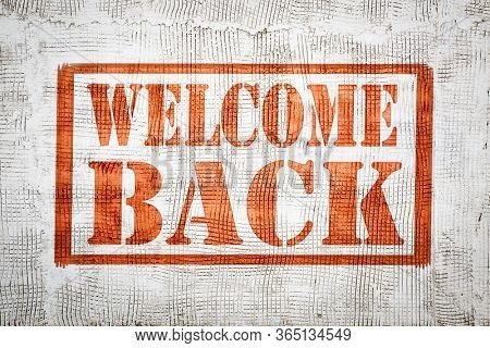 welcome back graffiti  sign - red stencil text on a stucco wall, hospitality and business reopening concept