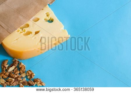 Maasdam Cheese With Wallnuts On A Blue With Copy Space.