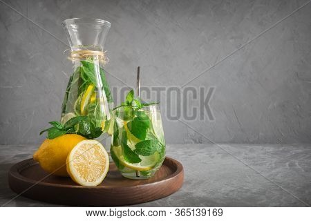 Detox Water Or Lemonade With Lemon Mint, Citrics In Glass On Grey Background. Close Up. Horizontal S