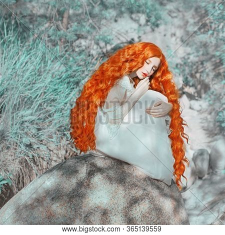 Young Beautiful Renaissance Red-haired Girl With Very Long Curly Hair Sitting On A Rock. A Fairy-tal