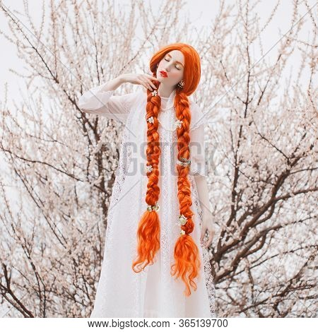 Young Beautiful Unusual Redhead Girl With Curly Hair Braided In Plait On A Spring Background. A Woma