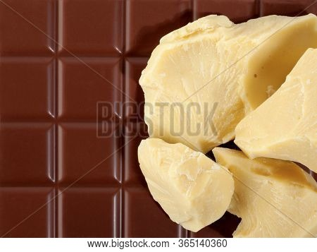 Pieces Of Natural Cocoa Butter On Bar Of Milk Chocolate. Macro Photo