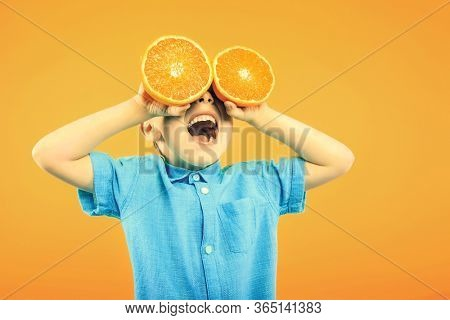 Happy cute boy is having fun played with fruit orange on yellow background wall. Bright photo of a boy. Colored panorama photo.
