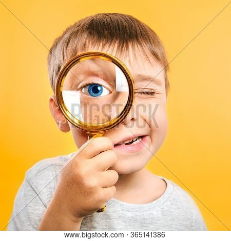 Child see through magnifying glass on the color yellow backgrounds. Big kid eye