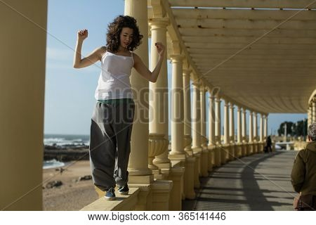 Mixed-race asian woman walks along the railing of ocean promenade. Porto, Portugal.