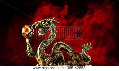Chinese Dragon Holding A Chrysanthemum Sphere With A Smokey Red Background.  Red Representing Luck,