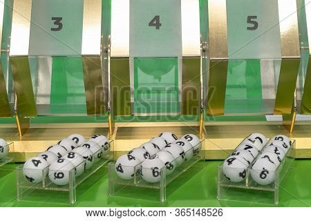 Sets Of Game White Balls With Numbers For A Lottery On A Green Table Near With A Lottery Drum