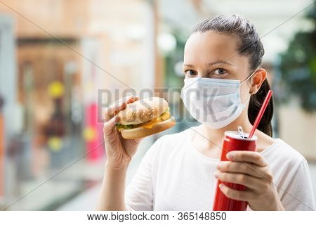 Woman Eating Fastfood Burger In Face Mask At Restaurant