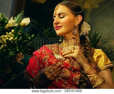 beautiful indian girl at home. Young woman model with golden jewelry set . Traditional Indian costume.
