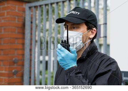Security Guard In Face Mask Talking On Walkie Talkie
