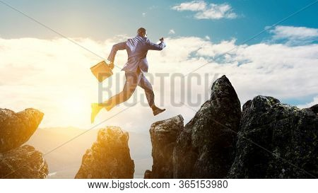 Back view of black businessman jumping over mountain stones