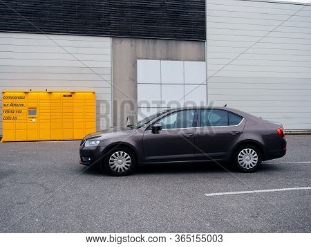 Paris, France - Mar 29, 2020: Side View Of New Brown Skoda Octavia Car In Front Of Yellow Amazon Loc