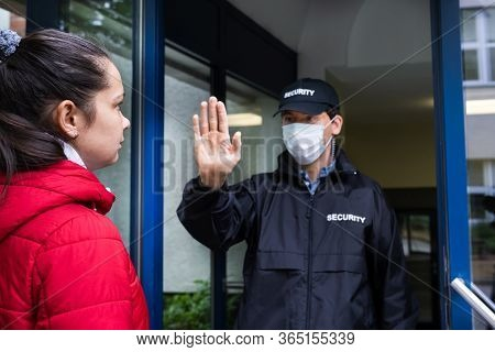 Security Guard In Uniform And Face Mask Making Stop Hand Gesture