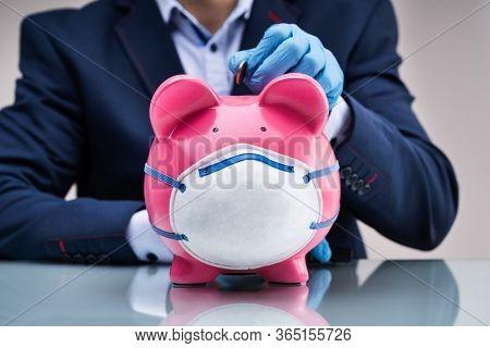 Inserting Coin In Piggybank To Save Money During Coronavirus Crisis