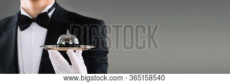 Waiter Or Butler With Hospitality Concierge Service Bell In Hand