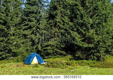 Tourist Tent Mountains Near The Forest. Tourist Tent Stands In A Clearing In The Mountains Under Gre