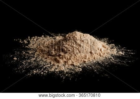 Spilled brown powder looking like unrefined heroin isolated on black background