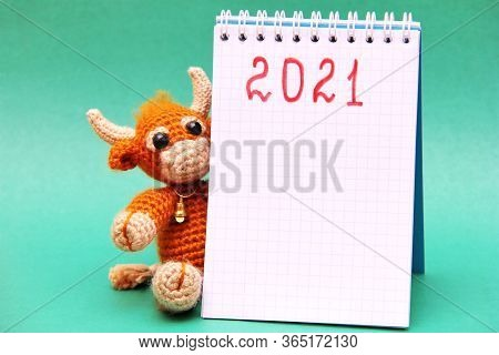 The Bull Is The Symbol Of The New Year 2021. A Knitted Brown Toy Bull Next To A Notepad With The Num