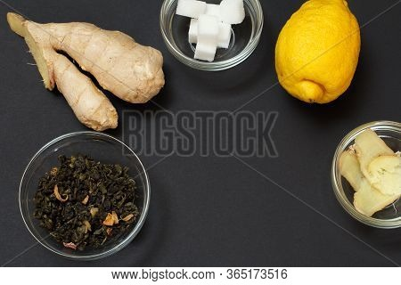 Health Remedy Foods For Cold And Flu Relief With Lemon, Ginger And Fruit Tea On A Black Background.