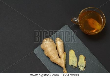 Health Remedy Foods For Cold And Flu Relief. Ginger And A Cup Of Tea With It On A Black Background.