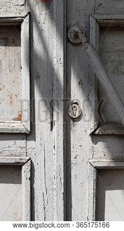 Details Of Old Wooden Door With Grey Flaking Paint On Door Panel Frames. Obsolete Rusty Metal Lock C