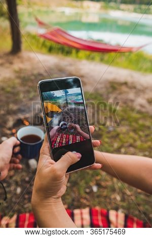 Woman Taking Picture Of Metal Camping Mugs On Phone