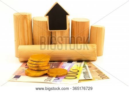 Paper Euro Money And Wooden Logs With Black Figure Of Home On White Background