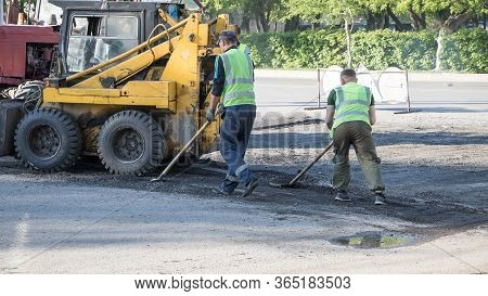 Moscow, Russia-07.05.2020: Road Works. Workers Repair The Road Surface And Asphalt The Street. Peopl